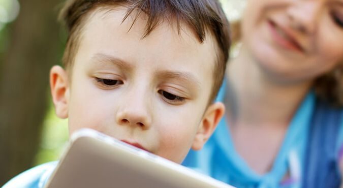 Niño se divierte con su iPad en compañía de su madre
